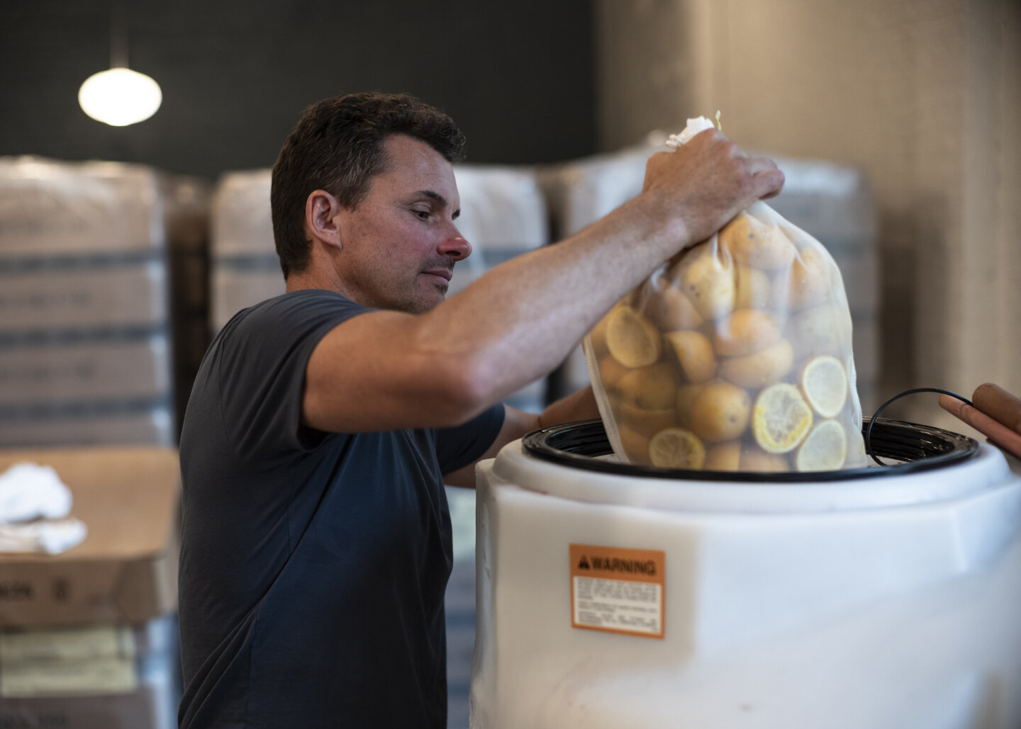 Darren lowers a 20-lb bag of orange peels, painstakingly sliced and juiced in advance, into the mulling tank.