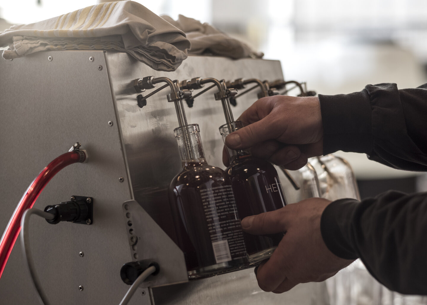 Kevin is a master at bottling, filling four bottles continuously and simultaneously, inserting a rubber stopper, and passing them down the line.